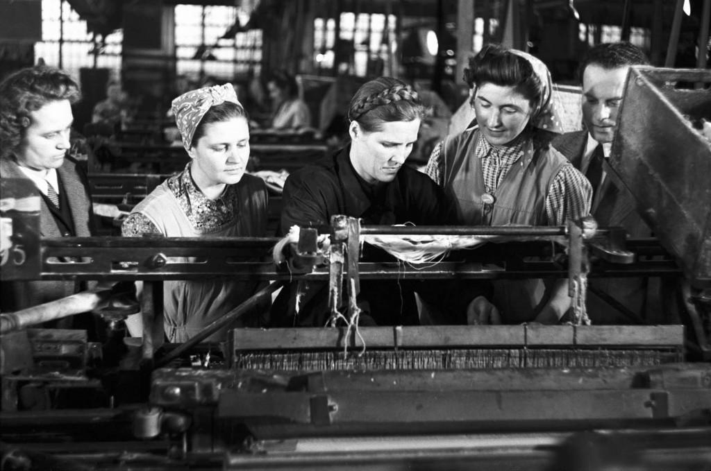 Budapest, 1952. február 25. Maria Vlagyimirovna Volkonszkaja, a kalinyi Vorosilov textilgyár sztahanovista szövőnője (b3), a Magyar-Szovjet Barátsági Hónap alkalmából hazánkban tartózkodó szovjet küldöttség tagja a Kelenföldi Textilkombinát Nemzeti Vállalat (Keltex) szövödéjében járva hasznos munkafogásokat mutat a magyar szövőnőknek: köztük Kun Rózsinak (pöttyös kendőben) és Büki Kálmánnénak. MTI Fotó/Magyar Fotó: Murai György